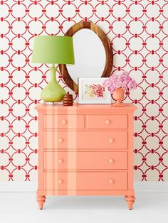 """Off-center peach stripes—which echo the streaks of the mirror's wood frame—and a lime green gourd lamp energize a coral dresser. Berry-hued paint, stenciled in a chain-link pattern on the wall, adds a graphic kick. PAINT on VASE Coral Reef by Benjamin Moore; Art: Fresh Floral by Kelly Ventura 11"""" x 14"""" framed print, $89, minted.com; Wall stencil: Chain Link Allover stencil, $40, cuttingedgestencils.com; Wall paint: Candy Apple by Glidden and White Dove by Benjamin Moore Striped Dresser, Coral Dresser, Dresser As Nightstand, Bedroom Dressers, Paleta Pantone, Peach Color Palettes, Peach Paint, Wood Framed Mirror, Living Room Remodel"""