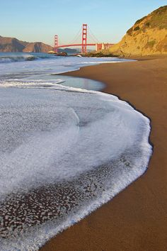 walking along North Baker Beach as the ocean leads to the bay, in San Francisco, CA
