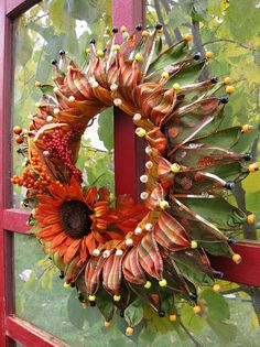 fall wreath - OMG this is so clever.  wired ribbon with a pony bead on the end. It looks like a sunflower.