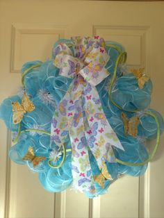 SPRING!!   Light blue and white deco mesh with 5 bejeweled gold butterflies, lime green glamour rope and a big white bow covered in glittery butterflies of pink, blue, green and yellow!