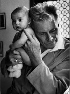 In lieu of a stethoscope, Albert-André Nast, a blind doctor in France, holds his ear to the back of a 3-month old, 1953.