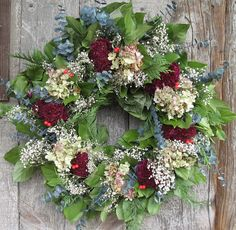 amgrowers.com.   Lemon leaf, eucalyptus and baby's breath base, decorated with deep red cockscomb, hydrangea, cedar and red berries.