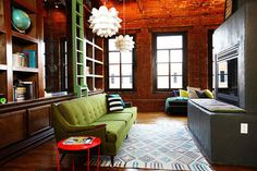 so much to love about this room. shelving w/ ladder, warm colors, green sofa, etc. etc.