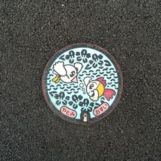 Kin-chan (golden fish) and Bun-chan (white Java spallow) manhole cover. Small one. Place: Yatomi city, Aichi, Japan.