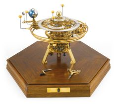 A Brass Timepiece-Driven Orrery --  Eric Watson, Oldham, circa 1985   from the central sun the Earth rotates on its axis and the moon rotates around the Earth, the five visible planets, Mercury, Venus, Mars, Jupiter and Saturn rotate in real time around the sun, the tripod base mounted on a sapele veneered hexagonal plinth, the moulded frieze with a brass drawer containing winder and manual crank, with a glazed cover   Sotheby's