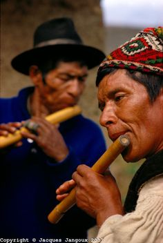 Quechua Indians playing flute at village festival, Bolivia