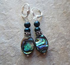 This listing is for a pair of abalone oval shell earrings with teal colored freshwater pearls. The shell ovals measure I've added antique silver spacer beads. The leverbacks are silver plated. Length of earrings - inches. Shop Sale, Shell Earrings, Abalone Shell, Green And Purple, Fresh Water, Turquoise Bracelet, Shells, Personalized Items, Pearls