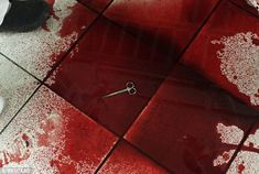 Sickening: Medical scissors lie in a puddle of blood on the floor of the emergency room in San Pedro Sula