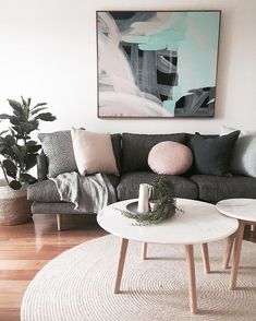Living room | Dark grey lounge, pink cushions, artwork, wood