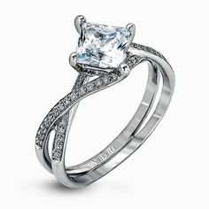 This dramatic white gold engagement ring is highlighted by .15 ctw of dazzling round cut white diamonds in a distinctive modern twist design.