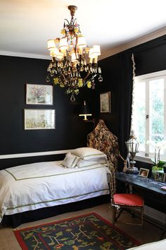 Black walls, chandelier, reading sconce by bed with black lampshade, sisal rug with colorful rug on top, fabric headboard, green-edged linens