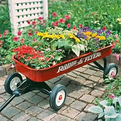 Garden on wheels  Plant a rainbow of annuals in a wagon for a portable garden. Be sure to drill a hole in the bottom of the wagon to provi...