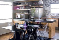 Com a demolição da parede entre a sala e a cozinha, os ambientes ficaram integrados. A bancada de concreto, com pintura de epóxi preto, e as prateleiras suspensas por cabos de aço dividem os espaços sem fechá-los. O projeto é assinado pelo Superlimão Studio.