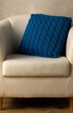 A lovely statement cable pillow knitting pattern is just the thing to perk up your neutral colored couch.