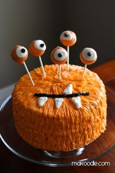 Orange Monster Cake | This creative orange monster cake is just the ticket for getting into the Halloween spirit.  There is no need for any special decorating skills, all you need are some tubes of icing or a piping bag fitted with a small tip.  The cake pop eyes balls are made from dipping them into orange and white candy melts with a chocolate chip for the pupil. @makoodle