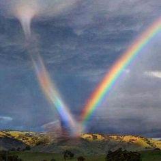 A rare sight, a tornado sucks in a bright rainbow.