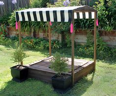 A DIY Sandbox Canopy with black and white stripes and hot pink tassels #LowesCreator