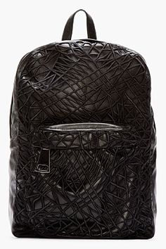 Buffed leather backpack in black. Gunmetal tone hardware. Leather carry handle at top. Adjustable padded shoulder straps at back.