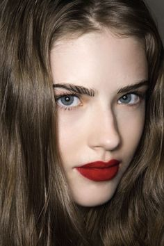 Striking matte red lip. Love the combination of simple, satin skin and thick, strong brows, too.
