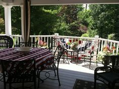 Fourth of July bunting, flags and decor on covered porch, looking out from house onto uncovered balcony