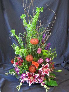 A stunning alter arrangement with Bells of Ireland, Stargazer Lilies, Proteas, Roses, Liatris, Kermits, Hypericum, Dendrobium Orchids