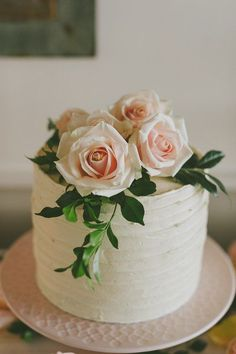 Layer cake with fresh pink roses and greenery