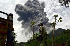 Indonesian farmers rush to harvest crops in the district of Karo as an ash cloud rises during a fresh eruption of the Mount Sinabung volcano, on September 17, 2013. Thousands of villagers fled after Mount Sinabung's series of volcanic eruptions on Indonesia's Sumatra island, spewing rocks and red-hot ash onto surrounding villages, officials said.