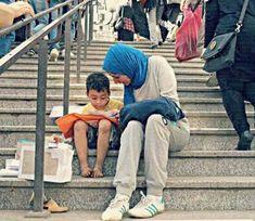 Una joven egipcia ayuda al hijo de un vendedor ambulante a aprender a leer.