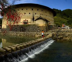 """Outsiders are most likely marveled at Tulou's odd-looking appearance and sophisticated structure. A Tulou is usually large, round or square, built into three to five stories (measuring 70 meters), housing for up to 80 families. The load-bearing rammed earth walls are as thick as 1.8m, enclosing smaller interior structures for storing items and raise livestock. With such a rigorous setting, this special building is like """"a little kingdom for the family"""" or """"bustling small city."""""""