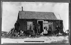 10. Unknown Location, 1882. A pioneer family poses outside their sod house.