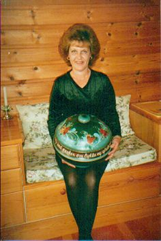 Joan Dahl in Norway holding a large bowl which is featured on the front  cover of one of her Hard Cover Rosemaling books.    Click On -> Rosemal.Com