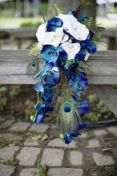 DIY Bridal Bouquet.  Create this gorgeous bouquet with high-quality silk flowers from Afloral.com.  This bouquet is made out of the Sophia Open Rose in White Cream, the Blue Phalaenopsis Silk Orchid Spray, Natural Peacock Feathers, and Lace or Maidenhair