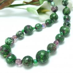 Ruby in Zoisite 18 inch beaded gemstone necklace. A beautiful combination of ruby reds and vibrant greens, accented with amethyst Czech Fire-Polished AB Crystals and teardrop green glass beads.  Ruby in Zoisite, also called Anyolite, is a combination fiery Ruby and earthy green Zoisite. This stone contains small Ruby crystals that have become embedded in the mineral Zoisite.  * Ruby in Zoisite Necklace 18 inch adjustable to 16 inch. * Sterling silver clasp and chain. * Large stone beads are…
