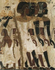 Part of a scene of Nubian Emissaries bearing tribute to Pharaoh. Just behind the walking figures can be seen a gold plate bearing large rings made of Nubian gold, upheld by two hands.