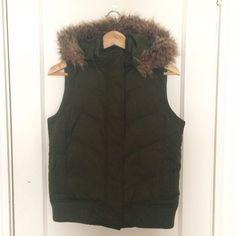GAP winter vest Olive green winter vest from Gap. Women's size XS. Detachable faux fur trimmed hood. Full zip & snaps up front. 2 hand pockets and one small pocket inside. Could fit a size small also, it is not slim fit. Small amount of pilling on bottom band, but overall in great used condition. GAP Jackets & Coats Vests