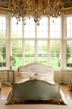 lovely French bedroom with extraordinary view, but the space needs the warmth of curtains. Either light and airy ones for summer that blow in the breezes and heavy ones for winter to block out the chill.