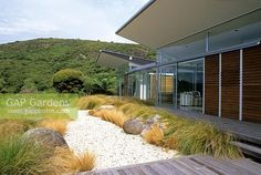 Garden view with boulders and native grasses contrasting with modern building in Piha, New Zealand. - Image No: 0053636 - GAP Gardens, garden and plant stock photography Landscape Plans, Garden Landscape Design, Garden Landscaping, Dry Garden, Home And Garden, Garden Grass, Outdoor Spaces, Outdoor Living, Outdoor Decor