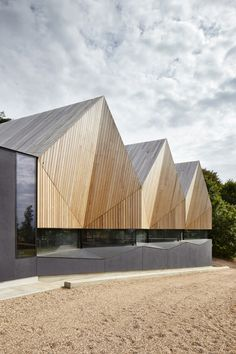 Angular wooden roof reduces sound reverberation inside swimming pool by Duggan Morris.
