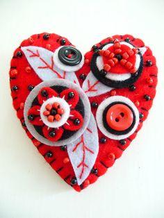 Corazón de fieltro rojo, negro y blanco con botones y abalorios