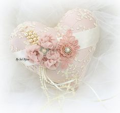 ***Ready To Ship. This listing is for 1 heart-shaped ring pillow, as shown in the photos. This pillow can be made in any color combination. This is one luxurious vintage-inspired ring bearer pillow! Crafted with ivory embroidered lace over rose satin, this heart-shaped, and one-of-a-kind piece features exquisite handmade flowers in rose chiffon, as well as a sparkly crystal and pearl jewel. My signature cluster of crystals and pearls, as well and lace leaves and more crystals complete the…