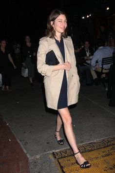 A trench, a dark dress, and ankle straps of course