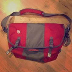 """Timbuk2 Classic Messenger Bag Timbuk2 brand """"Classic Messenger Bag"""" in red and grey. Used, but great condition. Great for multiple uses, including as a commute bag, travel bag, or even as a diaper bag! The outer shell is water resistant, to keep the items inside nice and dry. There's tons of space inside and multiple features to keep you organized (like pen holders)! The first photo is the actual color being sold. The other photos are for size and features. Timbuk2 Bags Laptop Bags"""