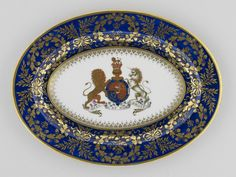 A Worcester porcelain oval plate with a gilt rim made c.1805; it bears the Royal Arms and supporters; the border comprises laurel branches and oak leaves enclosing floral emblems or cyphers of King George III. (Royal Collection)
