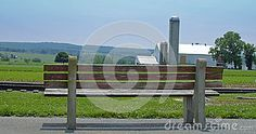A picture of a bench on a farm next to a railroad track