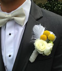 Yellow, white and grey boutonnière of ranunculus, billy balls and dusty miller, with a white feather and grey velvet stem wrap | By Forget Me Not Floral Design