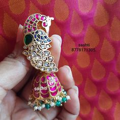PEACOCK BEAUTY . Stunning silver jumkhi with gold polish. Earrings studded with multi precious stones. Jumkhi with peacock design at studs. 06 August 2019