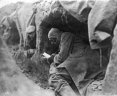 A soldier in a trench during the First World War writes letters home, 1914.