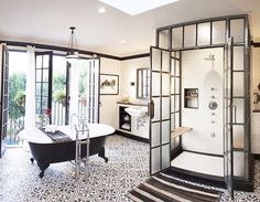 Spanish + industrial black and white bathroom with steel frame doors