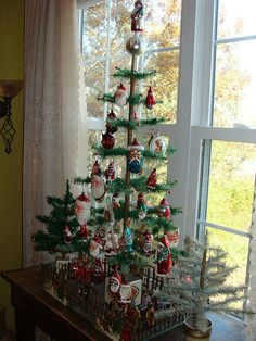 Feather Tree filled with Santa ornaments. Lovely fence around it with Santas ...Beautiful Display
