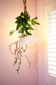 DIY Hanging Flower Light Fixture | Wrap some faux stems into a bouquet and add a power cord and lightbulb for a beautiful, whimsical light for your home.